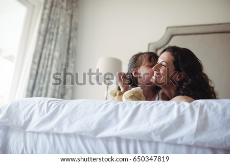 Daughter kissing her mother on cheek in bedroom at home #650347819