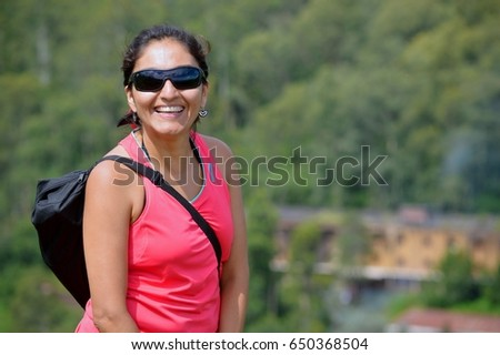 Beautiful happy woman walking on green hills #650368504