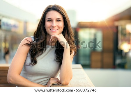 Genuine natural portrait of brunette woman happy and smiling on rooftop of new modern home Royalty-Free Stock Photo #650372746