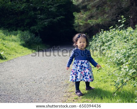 baby girl playing meadow on sunny day #650394436