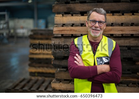 Portrait of male factory worker standing with arms crossed in drinks production factory Royalty-Free Stock Photo #650396473