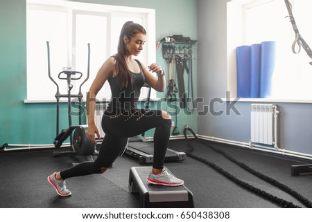 young fitness woman in the gym. A young athlete trains in the gymnasium. Power training. A warm-up in the gym. #650438308