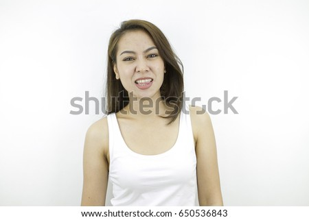 Show tongue for funny reaction with good looking face, pose by lifestyle of asian beautiful woman portrait in casual dress looking front, standing and thinking in grey background. #650536843
