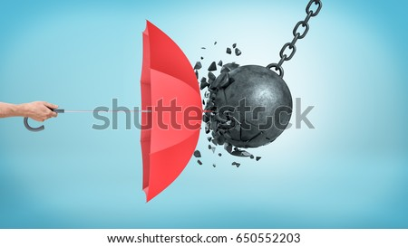 A male hand holding an open red umbrella which protects from a collision with a broken wrecking ball. Insurance and protection. Safety measures. IT defense. Royalty-Free Stock Photo #650552203