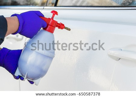 Male hands in blue gloves holding apparatus for spraying foam. Car wash. #650587378
