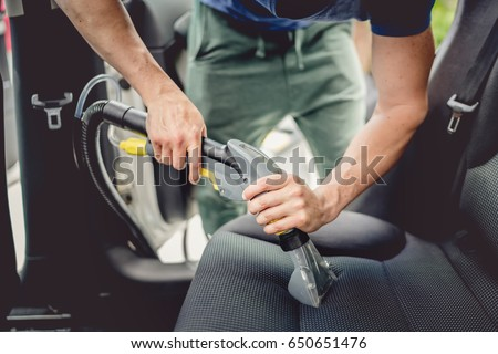 Details of car cleaning - male using professional steam vacuum for dirty car interior Royalty-Free Stock Photo #650651476