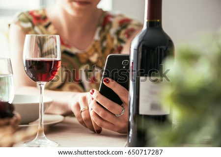 Woman having lunch at the restaurant and using a wine app with his smartphone, she is scanning the wine bottle label