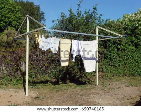 Laundry drying outdoor on homemade metal stands and frame with ropes #650740165