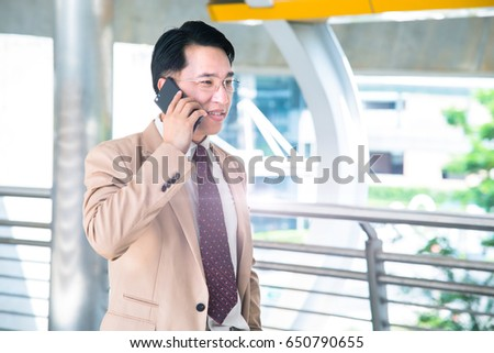 A handsome asian businessman using his mobile phone and standing on the street. #650790655
