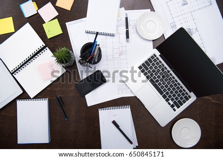 top view of laptop, smartphone, notepads and office supplies on tabletop at workspace #650845171