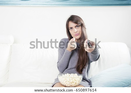 Beautiful young woman watching TV and eating popcorn #650897614