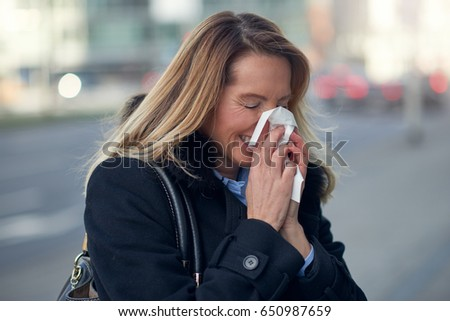 Woman with a seasonal winter cold blowing her nose on a handkerchief or tissue as she walks down an urban street in a health and medical concept #650987659