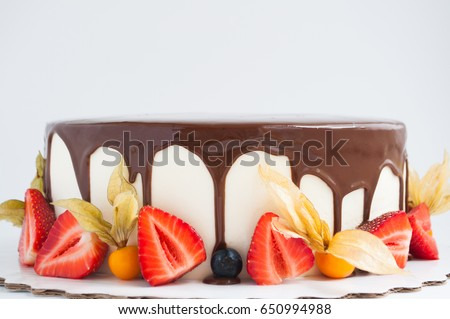 Birthday cake in chocolate with strawberries, blueberries and physalis on white background. Picture for a menu or a confectionery catalog.