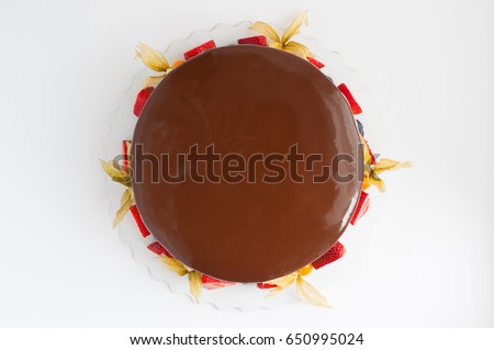 Birthday cake in chocolate with strawberries, blueberries and physalis on white background. Top view. Picture for a menu or a confectionery catalog.