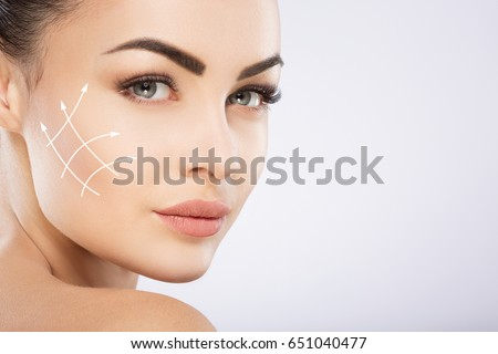 Young girl with black hair fixed behind, big eyes, thick eyebrows and naked shoulders at gray background, copy space, beauty photo, close up, antiaging concept, lifting arrows on face. #651040477