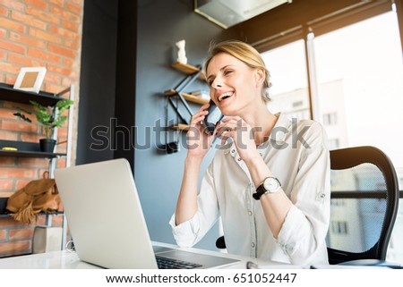 Cheerful lady sitting at table with mobile phone #651052447