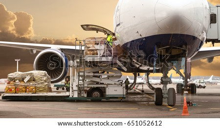 Loading cargo on the plane in airport, view through window Royalty-Free Stock Photo #651052612