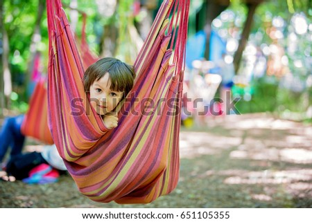 Cheerful child playing and lying inside the hammock, summertime #651105355