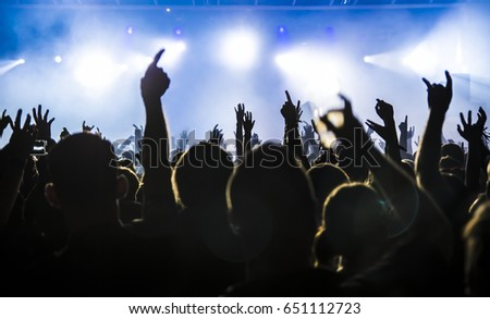 silhouettes of concert crowd in front of bright stage lights #651112723