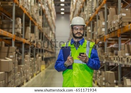 Warehouse worker in hard hat using mobile phone #651171934