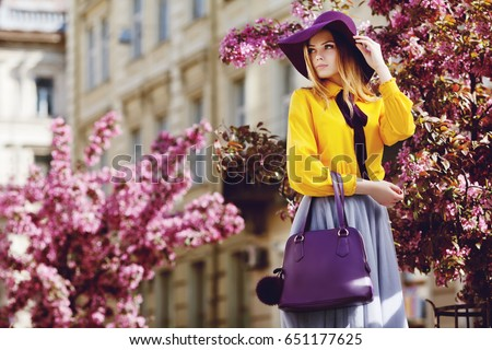 Outdoor portrait of young beautiful girl posing in street. Model wearing stylish hat, shirt, skirt, holding purple bag, handbag. City lifestyle. Female fashion concept. Copy, empty space for text  #651177625