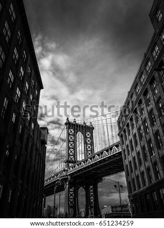 Manhattan bridge between buildings with cloudy sky in black and white #651234259