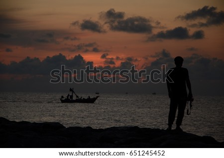 silhouette man on the shore take a photo a fishing boat