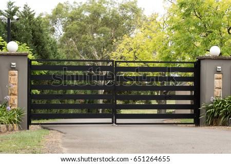 Black metal driveway entrance gates set in brick fence #651264655