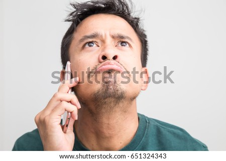 Mustache beard asian man feeling serious while talking on phone on white background #651324343