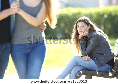 Sad single girl seeing an affectionate couple who are walking outdoors in a park #651333013