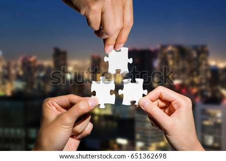 three hands holding piece of jigsaw puzzle on cityscape background. business partnership concept. business matching. #651362698