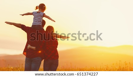 Happy family: mother father and child daughter on nature  on sunset #651374227
