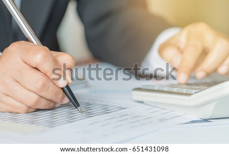Hand calculator and holding pen for analyzing financial data and counting on document chart, business concept. #651431098