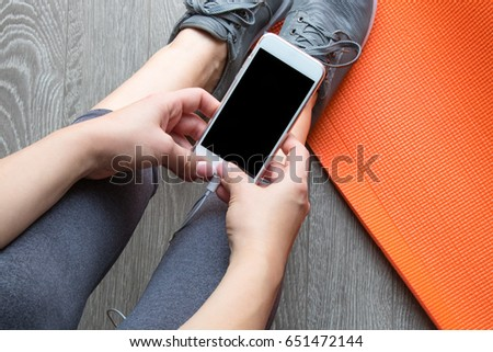 Girl has a rest after the training in the gym. Holds the smartphone in her hands #651472144