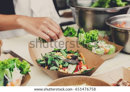 Street food festival, catering service. Vegetable salads in kraft paper plates sold outdoors at local market place, shallow depth of field #651476758