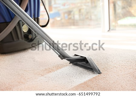 Cleaning service concept. Steam vapor cleaner removing dirt from carpet in flat, closeup Royalty-Free Stock Photo #651499792