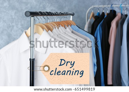 Concept of dry cleaning service. Hangers with clean clothes hanging on rack #651499819