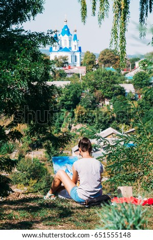 Talented Artist Girl in spruce green park draws oil-based paints with blue church domes in Kamianets-Podilskyi #651555148