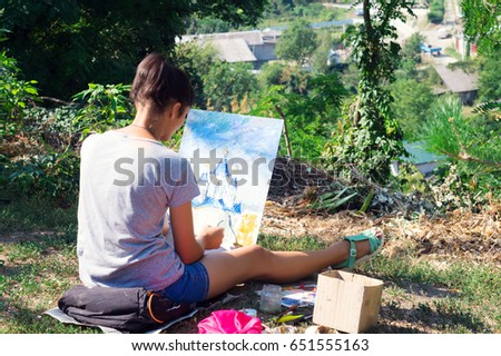 Talented Artist Girl in spruce green park draws oil-based paints with blue church domes in Kamianets-Podilskyi #651555163