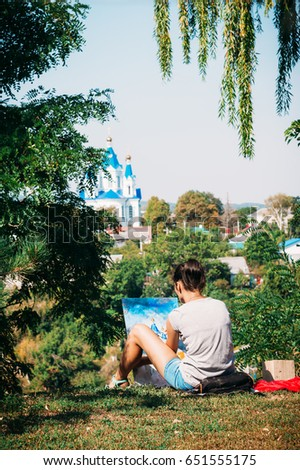 Talented Artist Girl in spruce green park draws oil-based paints with blue church domes in Kamianets-Podilskyi #651555175