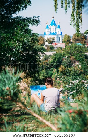 Talented Artist Girl in spruce green park draws oil-based paints with blue church domes in Kamianets-Podilskyi #651555187