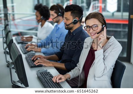 Smiling business executives with headsets using computers at desk in office #651645262