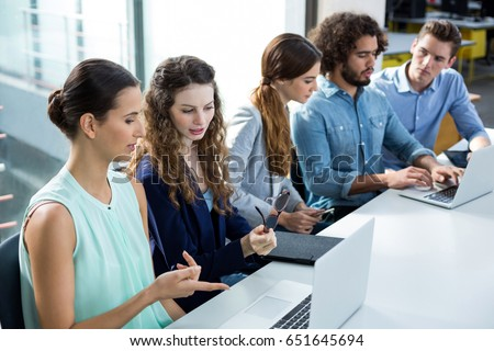 Business team discussing over laptop in meeting at office #651645694