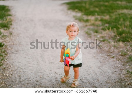 cute little girl in summer day holds windmill in hand #651667948