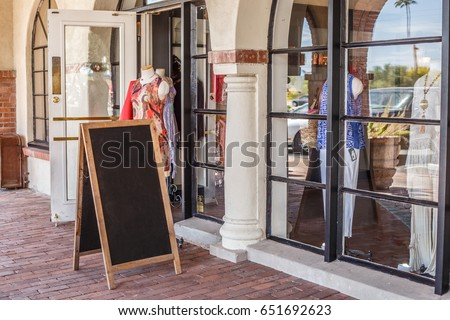 Blank Mock up Chalkboard Sandwich Sign Sitting On Display Outside Storefront Clothing Store with Open Door in Summertime