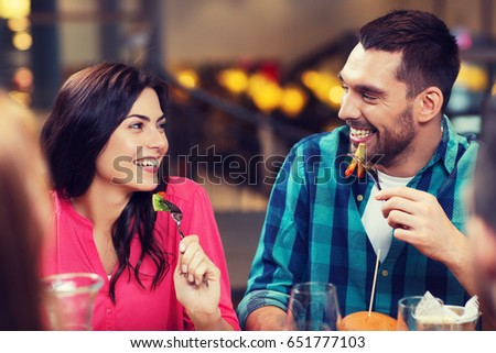 leisure, food and drinks, people and holidays concept - happy couple with friends having dinner at restaurant #651777103