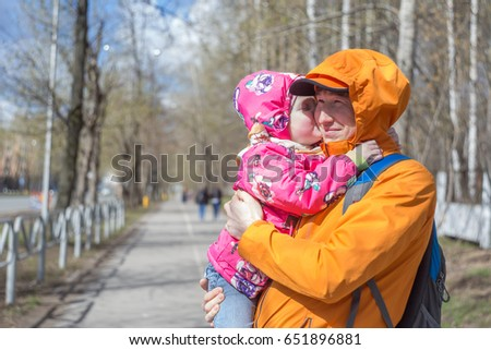 Dad is holding a daughter in his arms for a walk in the park. Spring day, family walk in nature, sunny. Daughter kissing daddy. #651896881
