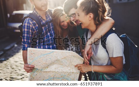 Young happy tourists sightseeing in city Royalty-Free Stock Photo #651937891