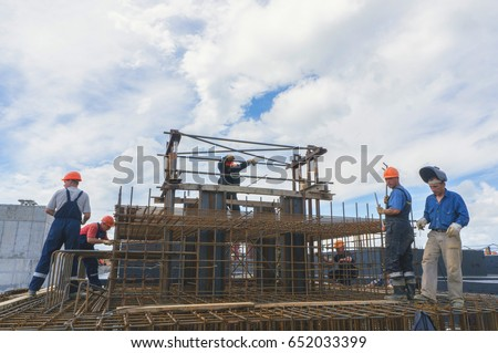 SOVETSKAYA GAVAN, RUSSIA - JULY 30, 2017: Workers make reinforcing cages of the foundation #652033399