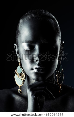 Close-up portrait of a gorgeous young woman with perfect black skin and silver glitter lips wearing beautiful earrings. Body painting project. Cosmetics and make-up. Jewelry and bijouterie.  #652064299